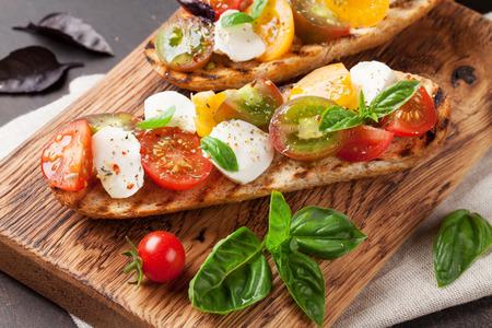 Bruschetta met cherrytomaatjes, mozzarella en basilicum op een houten bord. Caprese salade Stockfoto