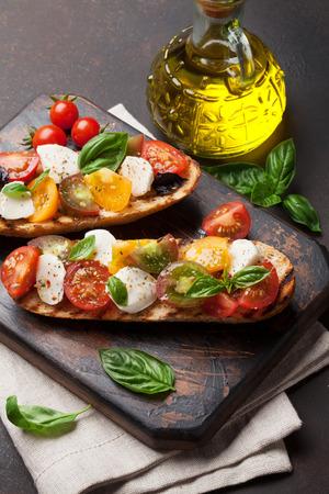 Bruschetta aux tomates cerises, mozzarella et basilic sur planche de bois. Caprese Salad Banque d'images - 82244829