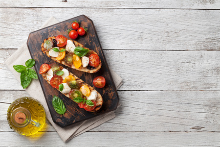 Bruschetta with cherry tomatoes, mozzarella and basil on wooden board. Caprese salad. Top view with copy space