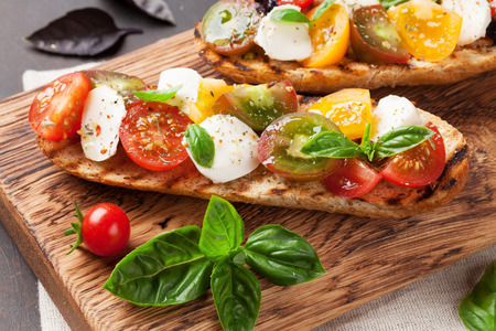 Bruschetta with cherry tomatoes, mozzarella and basil on wooden board. Caprese salad