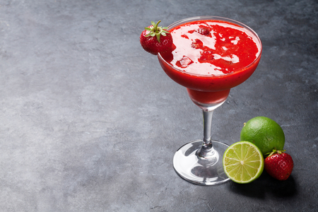 Strawberry margarita cocktail on dark stone table. With copy space