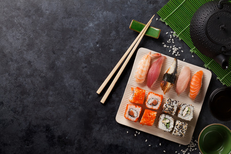 Set of sushi and maki roll and green tea on stone table. View with copy space Reklamní fotografie