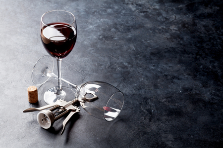 Red wine glasses and corkscrew on stone table. With copy space Stock Photo - 82339832