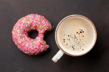 Coffee cup and pink donut on stone table. Top view Zdjęcie Seryjne
