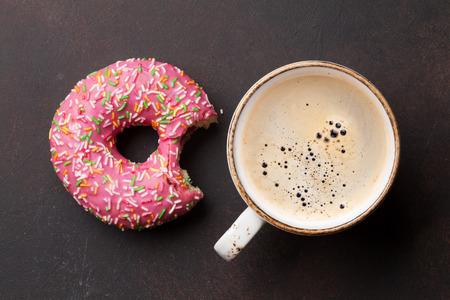 Koffiekopje en roze donut op stenen tafel. Bovenaanzicht