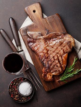T ボーン ステーキと赤ワインのガラス石のテーブルの上のグリル。トップ ビュー