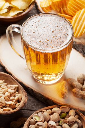 Lager beer mug and snacks on wooden table. Nuts, chips