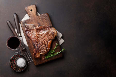 Grilled T-bone steak and red wine glass on stone table. Top view with copy space Stock Photo - 82722797
