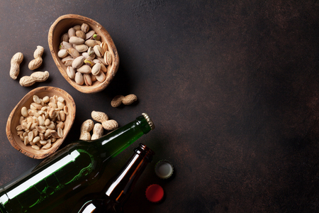 Lager beer and snacks on stone table. Various nuts. Top view with copy space