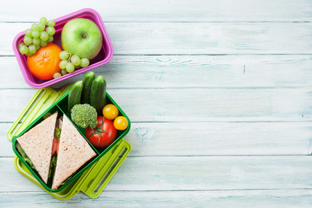 Lunch box with vegetables and sandwich on wooden background. Top view with space for your text Фото со стока