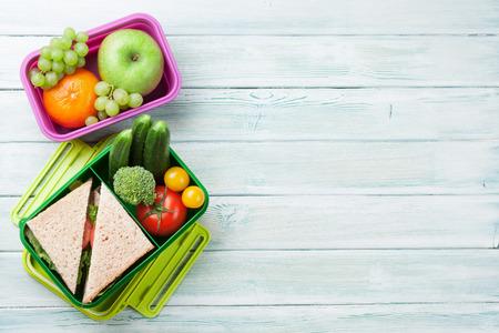 Lunchdoos met groenten en sandwich op houten achtergrond. Bovenaanzicht met ruimte voor uw tekst