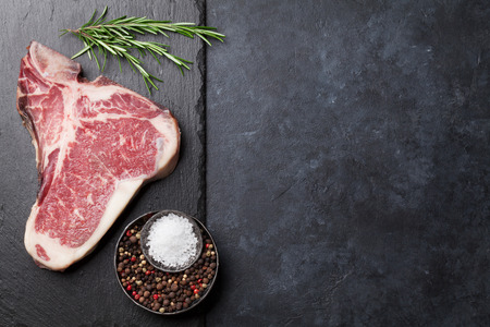 Raw T-bone steak cooking on stone table. Top view with copy space