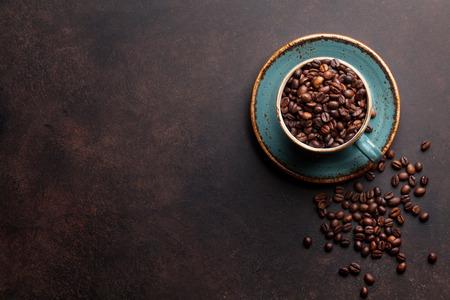 Tazza di caffè con fagioli arrostiti su fondo di pietra . Vista dall & # 39 ; alto con spazio di copia per il testo