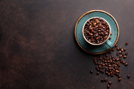 Coffee cup with roasted beans on stone background. Top view with copy space for your text