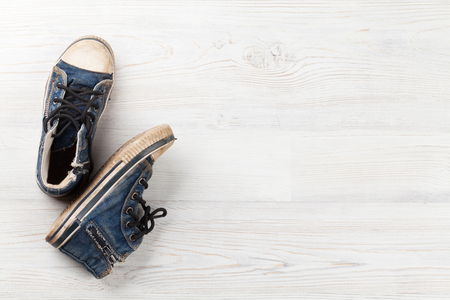 Pair of sneakers on wooden background. Top view with copy space