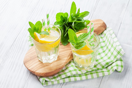 Lemonade with lemon, mint and ice on wooden table