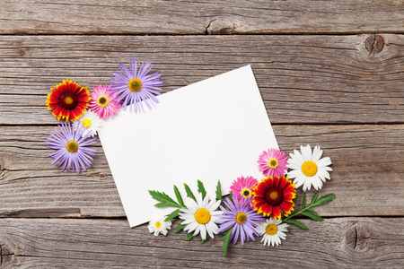 Blank greeting card and garden flowers on wooden texture. Top view with space for your text Stock Photo