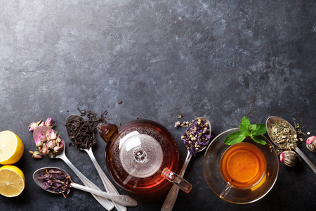 Tea cup, teapot and assortment of dry tea in spoons on stone table. Top view with copy space