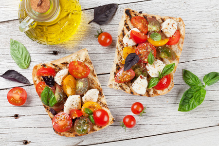 Bruschetta with cherry tomatoes, mozzarella and basil on wooden board. Caprese salad. Top view Banco de Imagens - 83573373