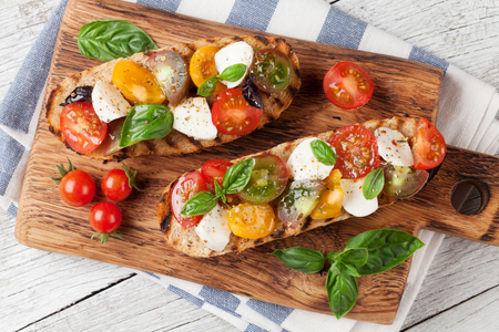 Bruschetta with cherry tomatoes, mozzarella and basil on wooden board. Caprese salad. Top view