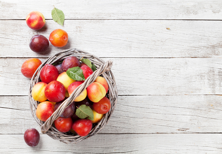 Fresh ripe peaches in basket on wooden table. Top view with space for your text