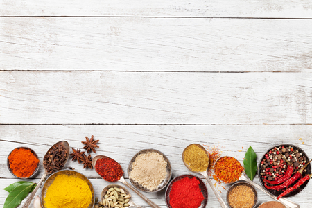 Various spices and herbs on wooden table. Top view with space for your text Stockfoto
