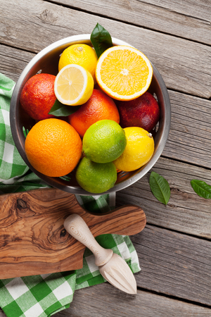 Fresh citrus fruits in colander on wooden table. Top view Stock Photo