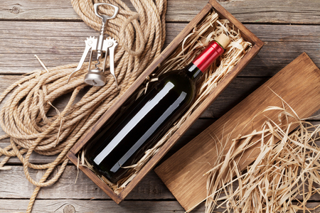 Red wine bottle in box on wooden table. Top view