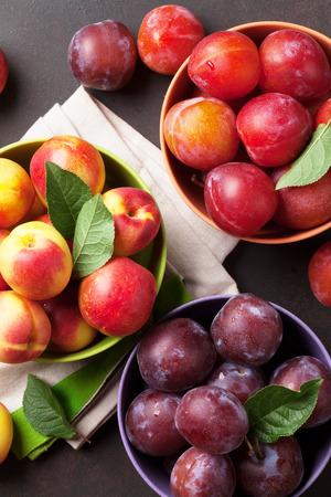 新鮮な熟した桃と石のテーブルに梅。トップ ビュー 写真素材