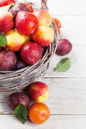 新鮮な熟した桃と木製のテーブル上のバスケットの梅 写真素材 - 84710753