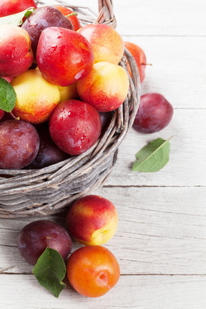 Fresh ripe peaches and plums in basket on wooden table Stock fotó