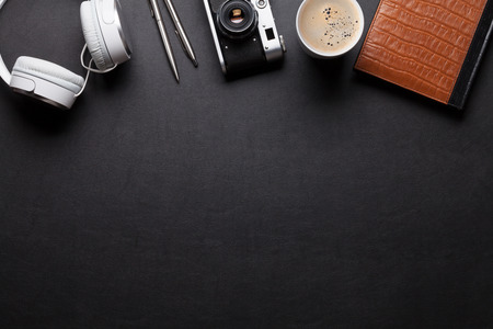 Office leather desk table with notepad, headphones, camera and coffee. Top view with copy space Stock Photo
