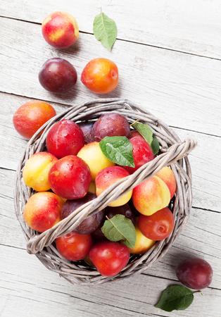 新鮮な熟した桃と木製のテーブル上のバスケットの梅。トップ ビュー 写真素材