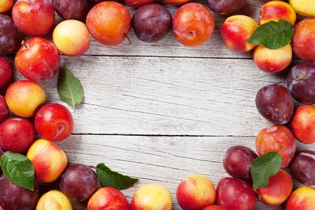 木製テーブルの上の新鮮な熟した桃、プラム フレーム。テキストのスペースのトップ ビュー