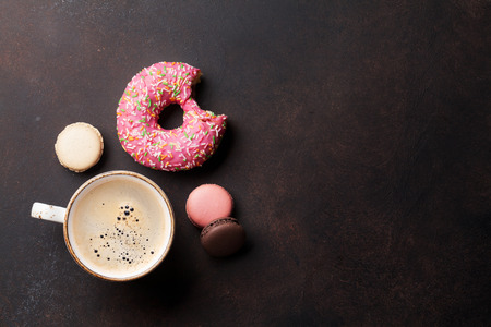 Coffee cup and sweets on stone table. Top view with copy space