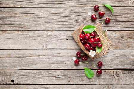 Fresh garden cherry in bowl on wooden table. Top view with copy space Stock fotó