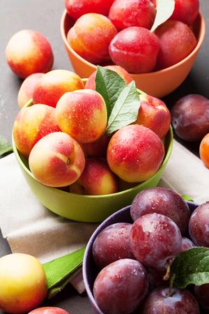 新鮮な熟した桃と石のテーブルに梅