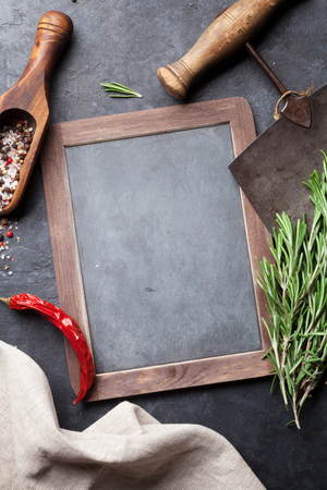 Herbs and spices cooking on stone table. Rosemary, pepper and salt. Top view with blackboard for your text Stock Photo