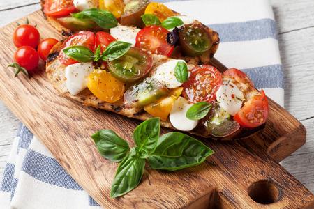 Bruschetta aux tomates cerises, mozzarella et basilic sur planche de bois. Caprese Salad Banque d'images - 85164255