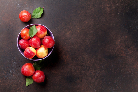 Fresh ripe plums on stone table. Top view with space for your text Stock Photo