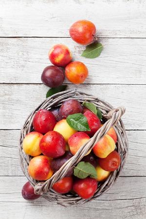 木製のテーブル上のバスケットの新鮮な熟した桃。トップ ビュー