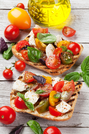 Bruschetta with cherry tomatoes, mozzarella and basil on wooden board