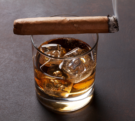 Whiskey with ice and cigar on stone table