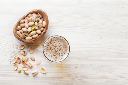Lager beer and nuts on wooden table. Top view with copy space