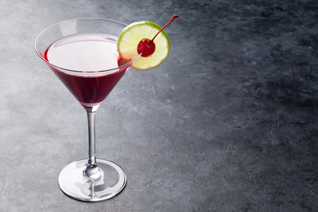 Cosmopolitan cocktail on dark stone table. With space for your text