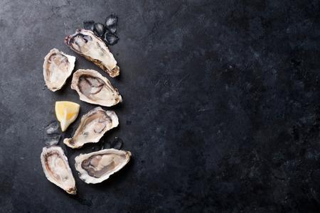 Geopende oesters, ijs en citroen op stenen tafel. Half dozijn. Bovenaanzicht met kopie ruimte Stockfoto