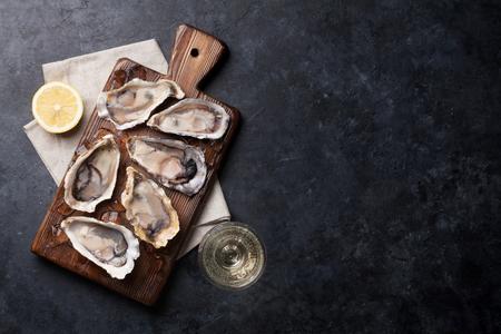 Geopende oesters, ijs en citroen aan boord. Bovenaanzicht met kopie ruimte Stockfoto