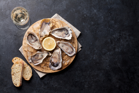 Opened oysters, ice and lemon on board. Top view with copy space Stock Photo