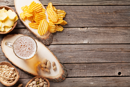Lager beer mug and snacks on wooden table. Nuts, chips. Top view with copy space