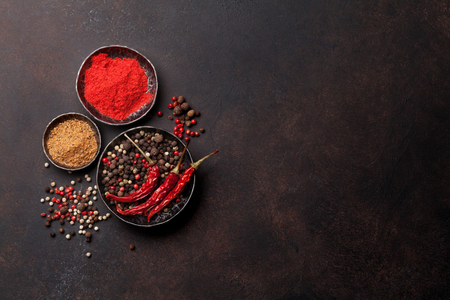 Colorful pepper. Various spices and herbs on stone table. Top view with space for your text